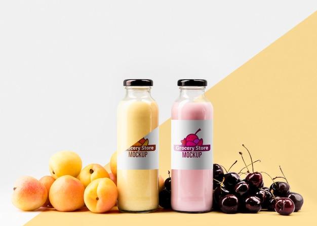 Vista frontal de botellas de jugo transparente con cerezas y melocotones