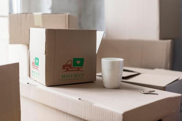 Vista frontal cajas de mudanza y taza de café