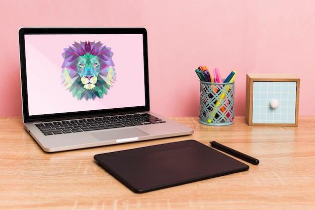 Vista frontal de la computadora portátil y el cuaderno de dibujo en el escritorio
