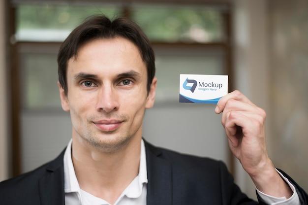 Vista frontal del empresario guapo con tarjeta de visita