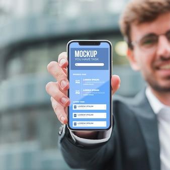 Vista frontal del empresario sonriente sosteniendo smartphone
