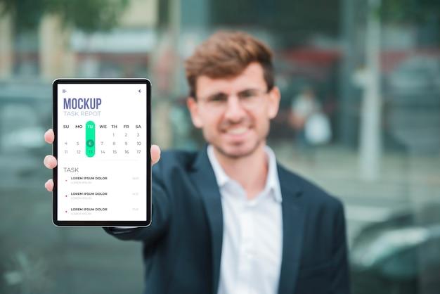 Vista frontal del empresario sonriente sosteniendo la tableta