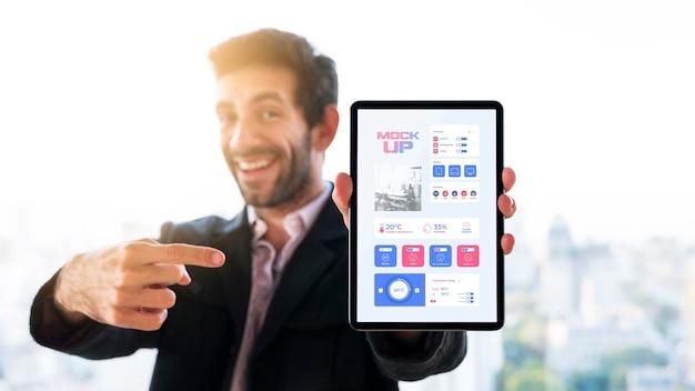 Vista frontal del empresario sosteniendo y apuntando a la tableta