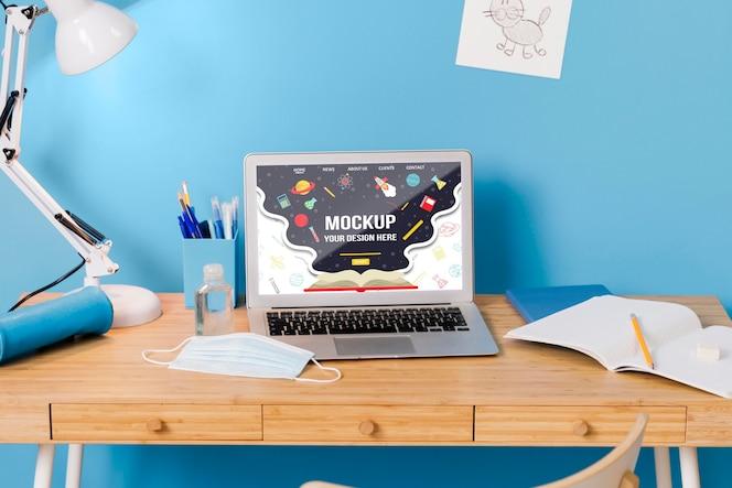 Vista frontal del escritorio de la escuela con laptop y lámpara