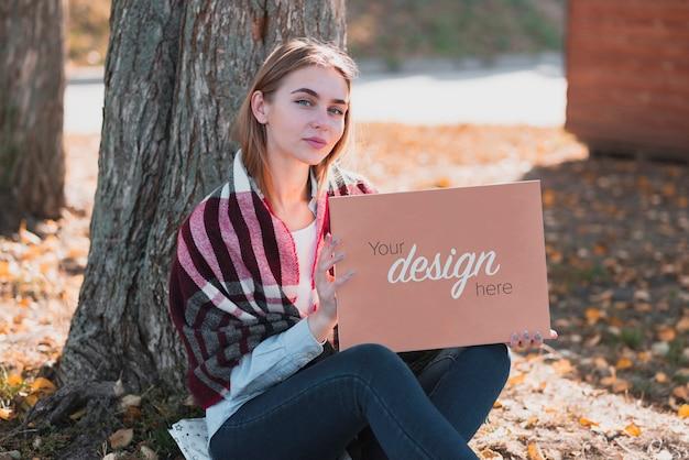Vista frontal hermosa chica rubia sosteniendo una maqueta de banner