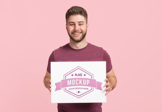 Vista frontal del hombre sosteniendo una tarjeta de maqueta de papelería