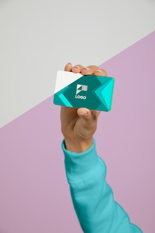 Vista frontal de la mano que sostiene la tarjeta de visita