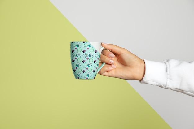 Vista frontal de la mano que sostiene la taza
