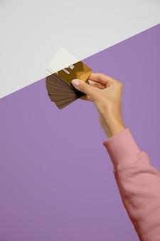 Vista frontal de la mano que sujeta las tarjetas de visita