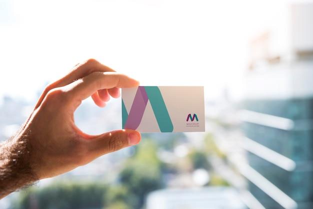Vista frontal de la mano sosteniendo una tarjeta de visita
