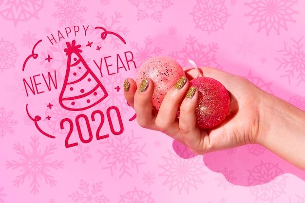 Vista frontal mano sujetando bolas de navidad con purpurina