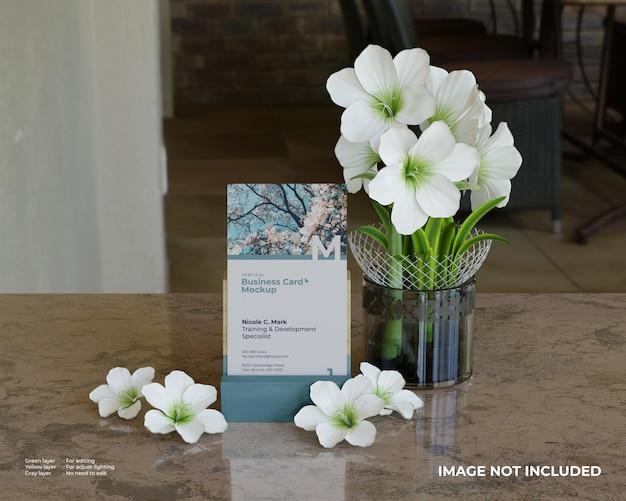 Vista frontal de la maqueta de tarjeta de visita vertical con soporte de madera y flores.