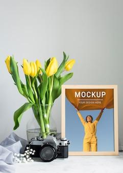 Vista frontal del marco con ramo de tulipanes en florero y cámara