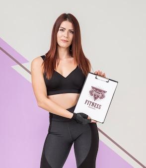 Vista frontal de la mujer atlética en ropa deportiva con bloc de notas