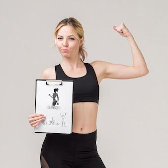 Vista frontal de la mujer fitness con bloc de notas y mostrando bíceps