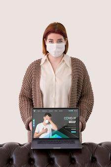 Vista frontal de la mujer con máscaras sosteniendo portátil