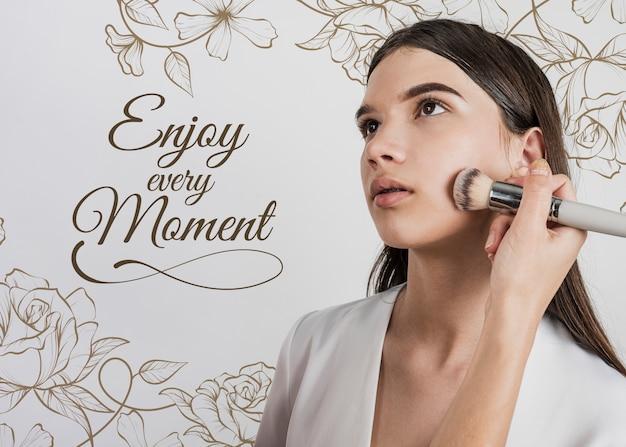 Vista frontal de la mujer con pincel de maquillaje