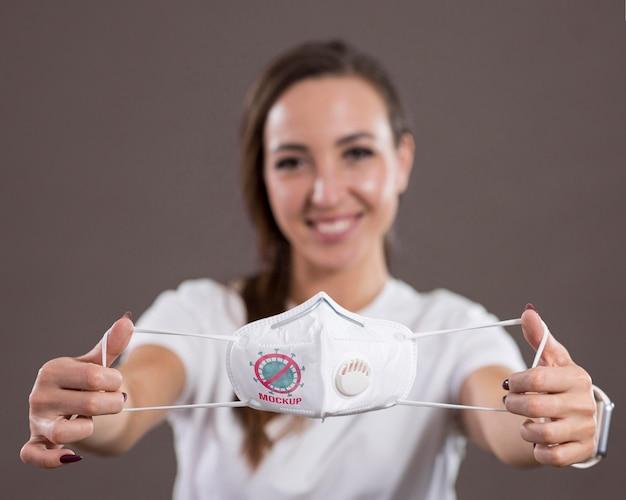 Vista frontal de la mujer sonriente sosteniendo una máscara