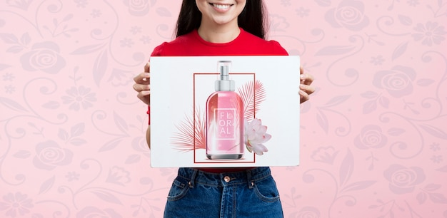 Vista frontal mujer sosteniendo un anuncio de maqueta para cosméticos