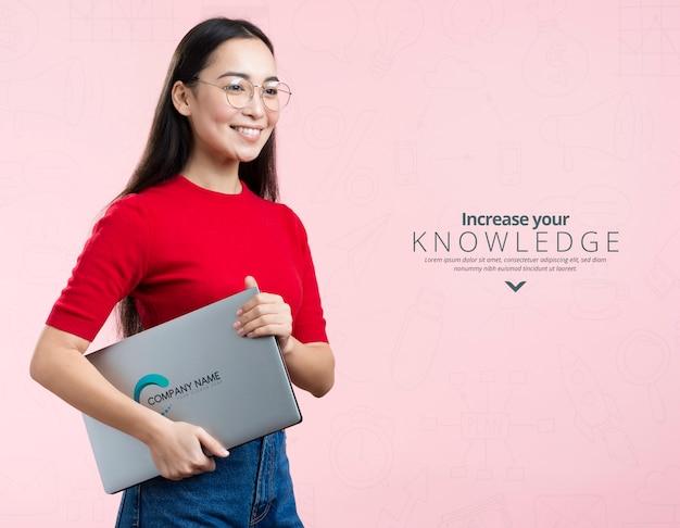 Vista frontal mujer sosteniendo un anuncio de maqueta y portátil