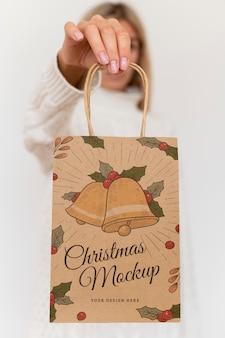 Vista frontal de la mujer sosteniendo una bolsa de papel de navidad