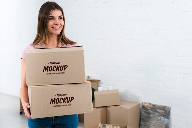 Vista frontal de la mujer sosteniendo la maqueta de cajas de mudanza