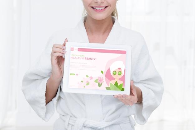 Vista frontal mujer sosteniendo tableta maqueta