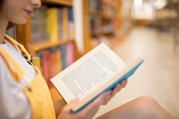 Vista frontal de la niña leyendo en la biblioteca