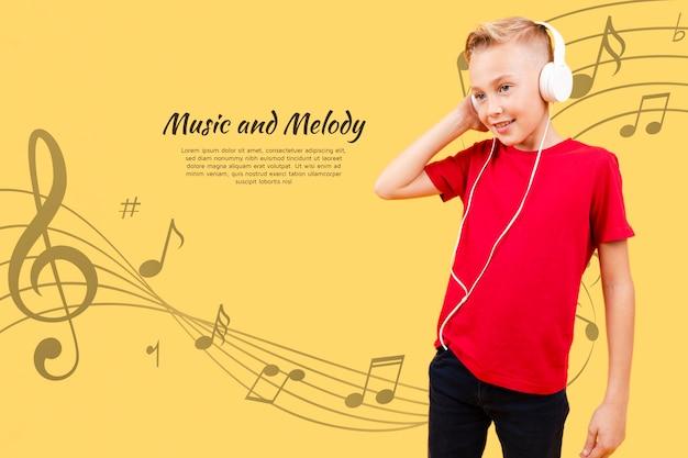 Vista frontal del niño escuchando música con auriculares