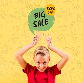 Vista frontal del niño haciendo signos de paz con gran venta