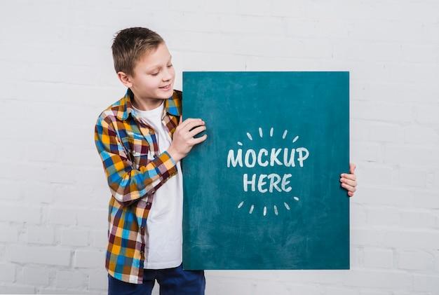Vista frontal niño joven con cartel de maqueta