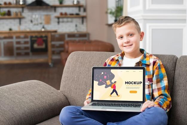 Vista frontal del niño sonriente en el sofá sosteniendo el portátil