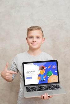 Vista frontal del niño sosteniendo y apuntando a la computadora portátil