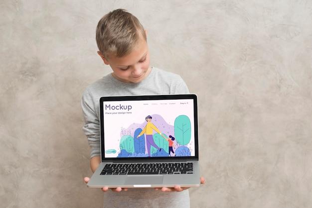 Vista frontal, de, niño, tenencia, computadora portátil