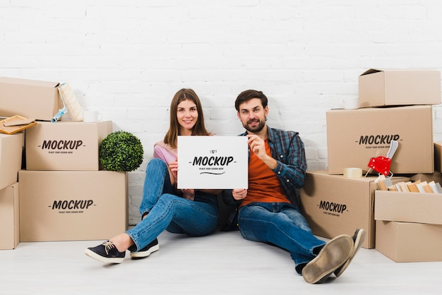 Vista frontal de la pareja posando con cajas de mudanza