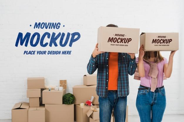 Vista frontal de la pareja posando con maqueta de cajas de mudanza