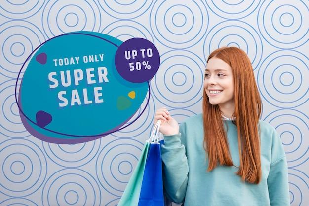 Vista frontal, plano medio de mujer sonriendo y sosteniendo bolsas de papel