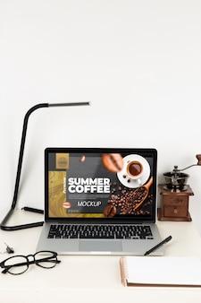Vista frontal del portátil en el escritorio con lámpara y gafas