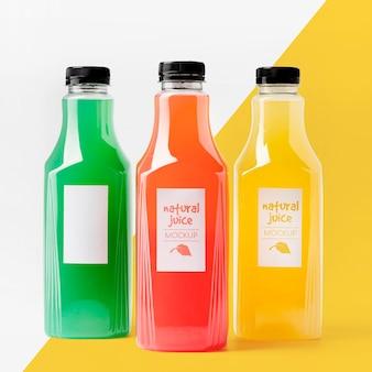 Vista frontal de la selección de botellas de jugo transparentes.