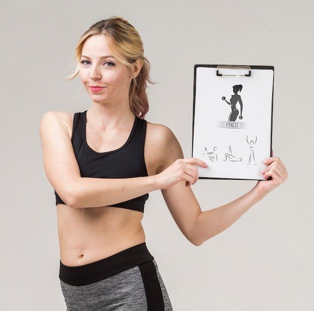 Vista frontal de smiley fitness mujer con bloc de notas
