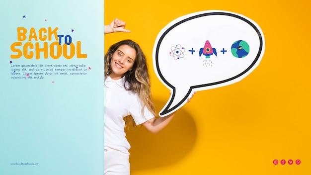 Vista frontal sonriente niña adolescente sosteniendo el bocadillo de diálogo