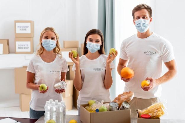 Vista frontal de voluntarios con máscaras médicas preparando donaciones de alimentos