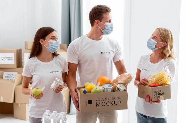 Vista frontal de voluntarios con máscaras médicas preparando donaciones de provisiones
