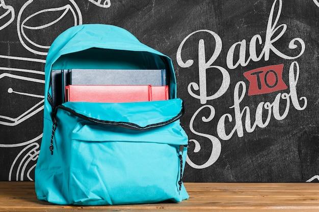 Vista frontal de vuelta a la mochila escolar con pizarra