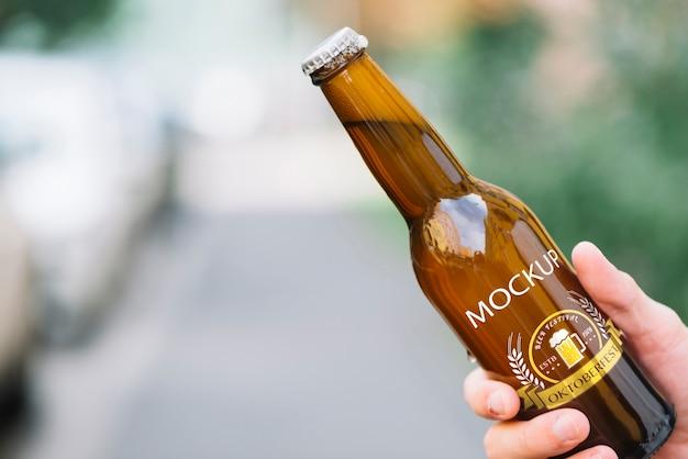 Vista frontale bottiglia di birra tenuta da persona