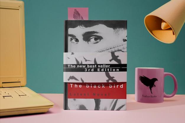 Vista frontale copertina di un libro e una tazza