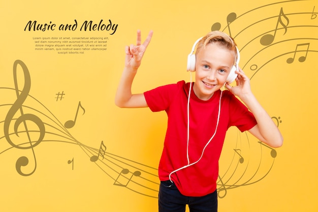 Vista frontale del bambino che ascolta la musica sulle cuffie e che fa il segno di pace