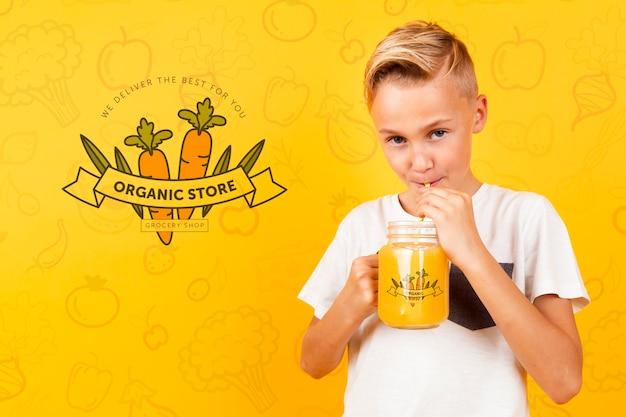 Vista frontale del bambino che beve il succo dal barattolo