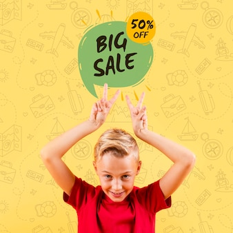 Vista frontale del bambino che fa i segni di pace con la grande vendita