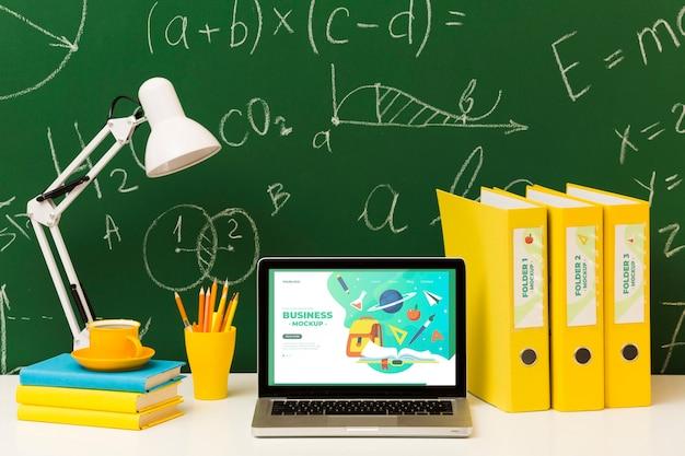 Vista frontale della scrivania con computer portatile e lampada
